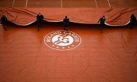 "(FILES) In this file photo taken on September 28, 2020 ground staff members take off the cover across the  Suzanne Lenglen court on Day 2 of The Roland Garros 2020 French Open tennis tournament in Paris. - The French government has discussed a possible ""delay of a few days"" of this year's French Open with the event organisers, the sports ministry told on April 6, 2021. (Photo by Anne-Christine POUJOULAT / AFP)"