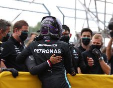 El piloto Lewis Hamilton  es felicitado por el equipo de Mercedes después de ganar la clasificación en Ímola. (Foto Prensa Libre: AFP).