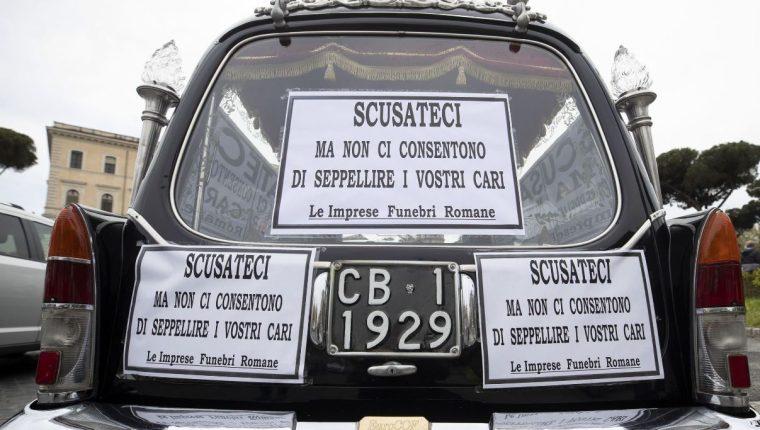 """Un carro fúnebre se encuentra en la Bocca della Verita con carteles que dicen """"Disculpe, pero no nos permiten enterrar a sus seres queridos"""". (Foto Prensa Libre: EFE)"""