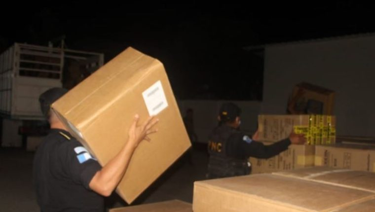 Agentes de la PNC custodian parte de los cigarrillos decomisados en Petén. (Foto Prensa Libre: PNC)