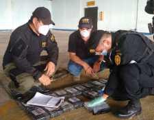 Fiscales del MP y agentes de la PNC durante el conteo de droga en el Comando Aéreo del Norte en Petén. (Foto Prensa Libre: MP)