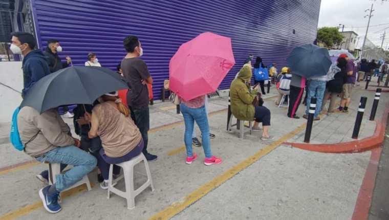 Bancos y sombrillas fueron usadas por las personas que esperaron por una dosis de la vacuna contra el covid-19 este Viernes Santo. Foto: María Reneé Barrientos