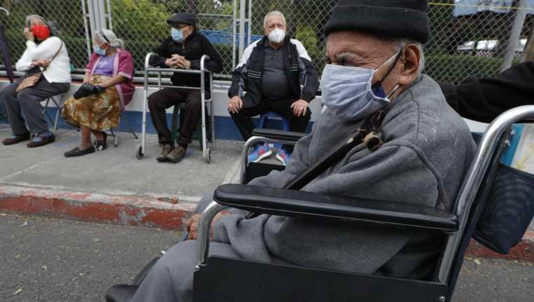 Personas de la tercera edad esperan a que continúe el proceso de vacunación el el puesto de Gerona. (Foto Prensa Libre: Esbin García)