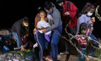 ROMA, TEXAS - APRIL 14: Parents check on their infant on the bank of the Rio Grande after they were smuggled across the U.S.-Mexico border on April 14, 2021 in Roma, Texas. A surge of mostly Central American immigrants crossing into the United States, including record numbers of children, has challenged U.S. immigration agencies along the U.S. southern border.   John Moore/Getty Images/AFP == FOR NEWSPAPERS, INTERNET, TELCOS & TELEVISION USE ONLY ==