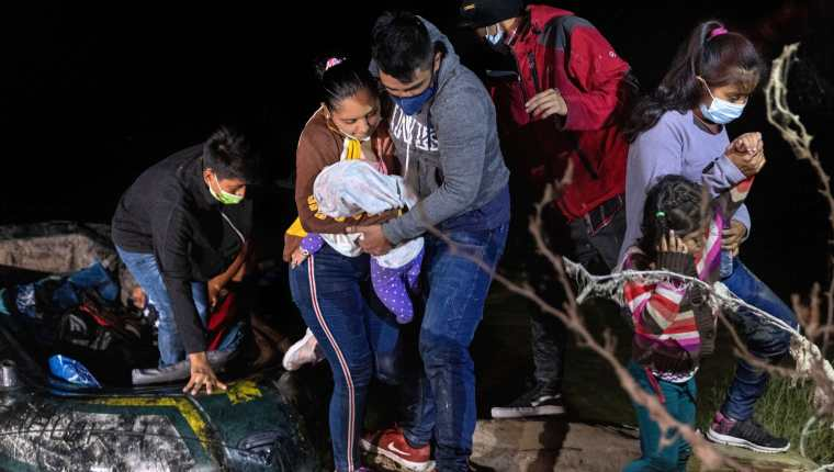 Los padres controlan a su bebé en la orilla del Río Grande después de que fueron contrabandeados a través de la frontera entre Estados Unidos y México en Roma, Texas. (Foto Prensa Libre: AFP)