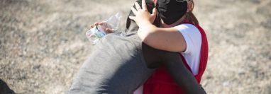 En esta foto, del 18 de mayo, capturada por Marcos Moreno, se ve a Luna Reyes, voluntaria de la Cruz Roja, brindándole ayuda al inmigrante que acababa de salir del mar. (MARCOS MORENO/ANADOLU AGENCY VIA GETTY IMAGES)