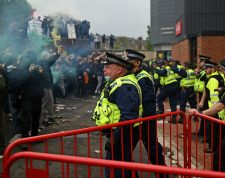 Police move people away from the stadium after a supporter's protest against Manchester United's owners, outside English Premier League club Manchester United's Old Trafford stadium in Manchester, north west England on May 2, 2021, ahead of their English Premier League fixture against Liverpool. - Manchester United were one of six Premier League teams to sign up to the breakaway European Super League tournament. But just 48 hours later the Super League collapsed as United and the rest of the English clubs pulled out. (Photo by Oli SCARFF / AFP)