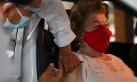 Una persona mayor de 70 años recibe la vacuna dentro de su vehículo, en el puesto de la Universidad Rafael Landívar. (Foto Prensa Libre: AFP)