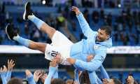 Players lifter Manchester City's Argentinian striker Sergio Aguero aloft during the trophy award ceremony after the English Premier League football match between Manchester City and Everton at the Etihad Stadium in Manchester, north west England, on May 23, 2021. (Photo by Dave Thompson / POOL / AFP) / RESTRICTED TO EDITORIAL USE. No use with unauthorized audio, video, data, fixture lists, club/league logos or 'live' services. Online in-match use limited to 120 images. An additional 40 images may be used in extra time. No video emulation. Social media in-match use limited to 120 images. An additional 40 images may be used in extra time. No use in betting publications, games or single club/league/player publications. /