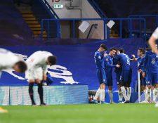 Los jugadores del Chelsea celebran la clasificación al final del partido, mientras los futbolistas merengues se lamentan. (Foto Prensa Libre: EFE)