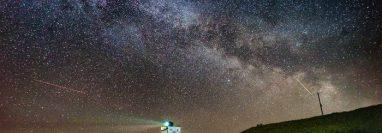 El núcleo de la Vía Láctea se hace visible en las primeras horas de la mañana del martes mientras se desplaza sobre el faro de Bamburgh, en Stag Rock, en Northumberland, Reino Unido.