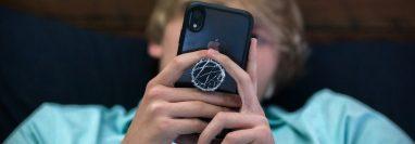 Bo Deal, un estudiante de primer año de secundaria en Metter, Georgia, mira su teléfono en su casa el 26 de marzo de 2021. Su familia restringió el uso de entretenimiento electrónico, excepto por su teléfono celular. (Stephen B. Morton/The New York Times)