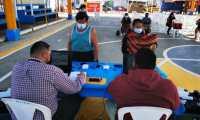 Vecinos de Villalobos, zona 12, acuden al puesto de empadronamiento móvil del TSE en la cancha municipal de esa colonia.  (Foto Prensa Libre: TSE)