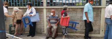 Muchos adultos mayores hicieron fila bajo el sol y debieron llevar bancos para descansar mientras esperaban para recibiré la primera dosis de la vacuna. (Foto Prensa Libre: María José Bonilla)