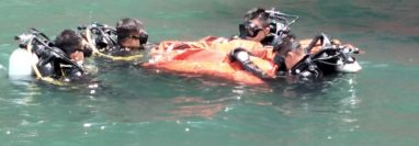 Buzos de la Marina del Ejército de Guatemala, recuperan las tres maletas que fueron localizadas bajo el barco que atracó en Puerto Quetzal, Escuintla. (Foto Prensa Libre: Ejército de Guatemala)