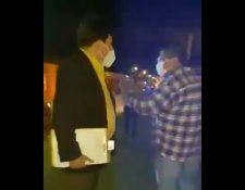 Osiel Calderón , juez nocturno de Asuntos Municipales de Antigua Guatemala, Sacatepéquez, izquierda, encara al vecino con el que discutía durante un operativo. (Foto Prensa Libre: Captura de video)