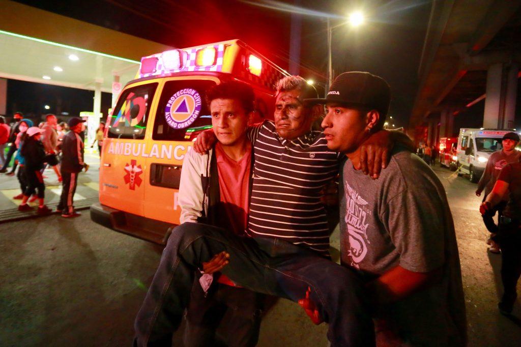 Dos jóvenes ayudan a un herido después de que una estructura del Sistema de Transporte Colectivo (METRO) colapsara junto con dos vagones en la Ciudad de México. (Foto Prensa Libre: EFE)