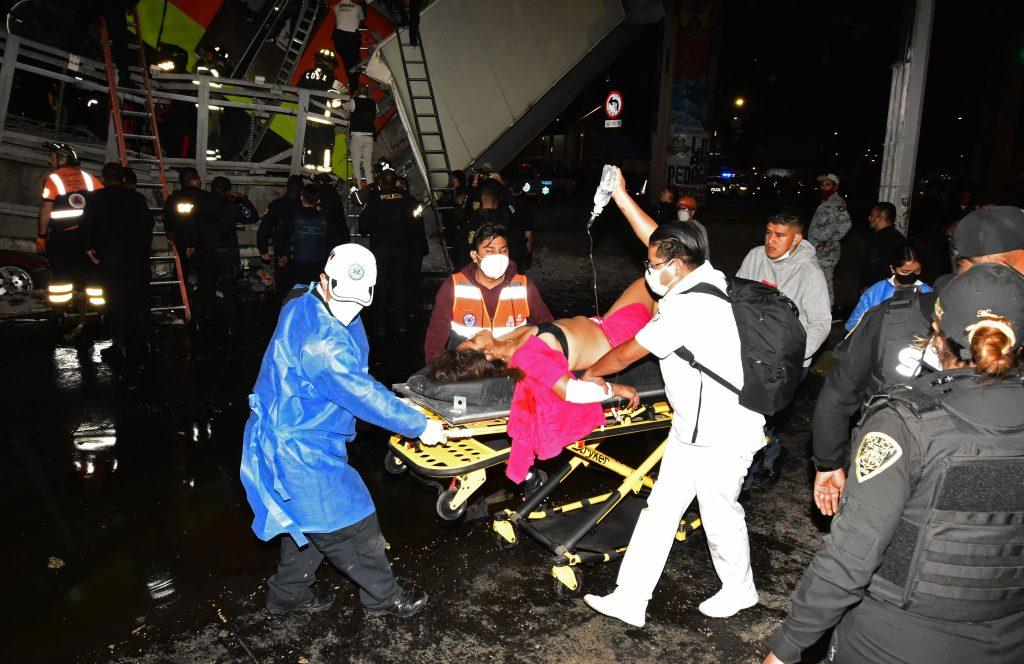 Miembros de los servicios de emergencia trasladan a una de las heridas tras el colapso de los vagones del metro  en la Ciudad de México. (Foto Prensa Libre: EFE)