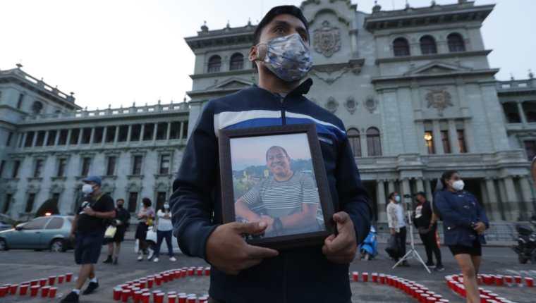 Alexander García, de 29 años, portaba una fotografía de su padre René fallecido hace un año por covid-19. (Foto Prensa Libre: Esbin García)