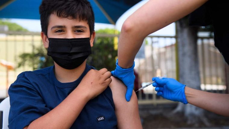 Simon Huizar, 13, receives a first dose of the Pfizer Covid-19 vaccine at a mobile vaccination clinic at the Weingart East Los Angeles YMCA on May 14, 2021 in Los Angeles, California. - The campaign to immunize America's 17 million adolescents aged 12-to-15 kicked off in full force on May 13. The YMCA of Metropolitan Los Angeles is working to overcome vaccine hesitancy and expand access in high risk communities with community vaccine clinics in the area. (Photo by Patrick T. FALLON / AFP)