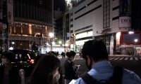 This picture taken on May 6, 2021 shows pedestrians illuminated by their mobile phones as the lights of nearby commercial buildings are seen switched off in Shibuya district in Tokyo, which are turned off after 8pm as part of measures to prevent attracting crowds amid a coronavirus state of emergency. (Photo by Philip FONG / AFP)