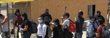 Policías escoltan desde una casa a más de un centenar de indocumentados secuestrados en Ciudad Juárez, Chihuahua. (Foto Prensa Libre: EFE)