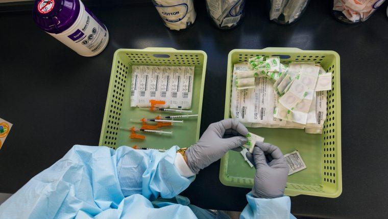 Un trabajador sanitario se prepara para administrar una dosis de la vacuna COVID-19 de Pfizer en Miami el 28 de mayo de 2021. (Foto Prensa Libre: Saul Martinez/The New York Times)