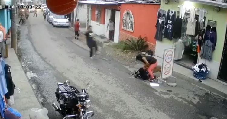 La madre trata de separar al perro del niño, pero le es imposible, mientras un hombre corre a ayudar. (Foto @Labrigadaz7/Facebook)