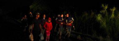 Un grupo de personas con hijos en sus brazos llega a un centro de procesamiento de migrantes que quieren asilarse en EE.UU., el 12 de mayo del 2021 en La Joya, Texas. (Foto Prensa Libre: Voz de América)