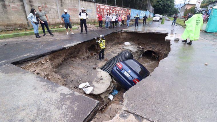 Un vehículo cayó al fondo de un hundimiento que hay desde hace varios días en la avenida Pablo VI y 2a. calle de la zona 7 de Mixco. (Foto Prensa Libre: Bomberos Voluntarios)