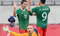 Mexico's midfielder Sebastian Cordova (L) celebrates scoring Mexico's second goal as France's goalkeeper Paul Bernardoni (BOTTOM) reacts during the Tokyo 2020 Olympic Games men's group A first round football match between Mexico and France at Tokyo Stadium in Tokyo on July 22, 2021. (Photo by FRANCK FIFE / AFP)