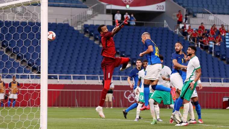 El delantero de Brasil, Richarlison,(de azul) cabecea ante l portero saudí Amin Bukhari. Foto Prensa Libre: AFP.