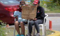 """AME9774. TEGUCIGALPA (HONDURAS), 30/06/2020.- Dos mujeres piden dinero para alimentar a sus hijos este martes, en Tegucigalpa (Honduras). El fenómeno de las caravanas de migrantes, que comenzó en octubre de 2018 en Honduras, ha representado un cambio en el sistema migratorio de Centroamérica, México y Estados Unidos y puso en evidencia """"su inoperancia"""" para dar respuesta a la problemática, alerta un estudio divulgado este martes. EFE/ Gustavo Amador"""