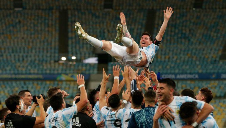 Jugadores de Argentina alzan a su compañero Lionel Messi durante la celebración del triunfo ante Brasil, en la final de la Copa América en el estadio Maracaná. Foto Prensa Libre: EFE.