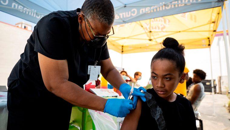 Joven de 12 años recibe vacuna contra el coronavirus en un puesto móvil en Crenshaw, en el Sur de Los Ángeles, California. (Foto Prensa Libre: EFE)