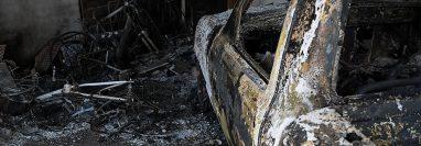 Un automóvil quemado es visto en la casa del ciudadano italiano Giorgio Scanu en el municipio de Santa Ana de Yusguare en Choluteca. Foto Prensa Libre: AFP.