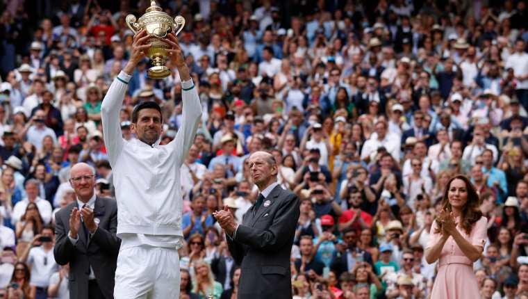 Novak Djokovic sostiene el trofeo de Winbledon después de haber vencido al italiano Matteo Berrettini en la final. Foto Prensa Libre: AFP.