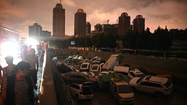 La gente mira los autos apilados unos sobre otros en la entrada de un túnel luego de una fuerte lluvia en Zhengzhou, en la provincia china de Henan (Foto: Prensa Libre. AFP).