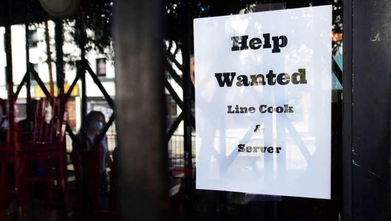 Personas caminan cerca de un restaurante con un rótulo pidiendo contratar a ayudantes. Foto: AFP