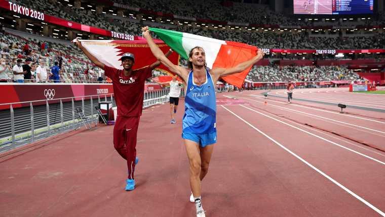 El catarí Mutaz Essa Barshim (I) y el italiano Gianmarco Tamberi celebran en el Estadio Olímpico de Tokio la medalla de oro que ganaron en salto alto. Foto Prensa Libre: AFP.