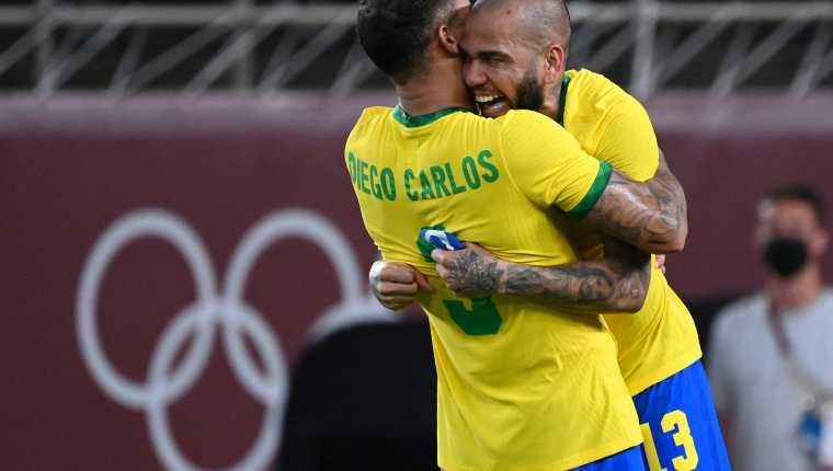 El veterano defensor brasileño Dani Alves (D) y Diego Carlos celebran el pase a la final del futbol masculino olímpico de Tokio 2020. Foto Prensa Libre: AFP.