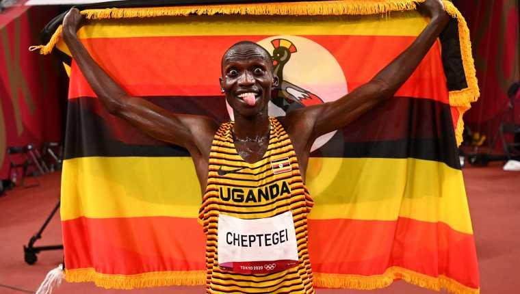 Joshua Cheptegei de Uganda con la bandera de su país la victoria en los 5000m que le dan su primera medalla de oro olímpica. Foto Prensa Libre: AFP.