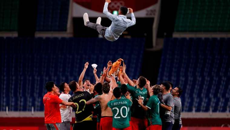 Los jugadores de México mantean a su entrenador Jaime Lozano (arriba) tras vencer a Japón en el encuentro por la medalla de bronce durante los Juegos Olímpicos de Tokio 2020, este viernes en el Estadio de Saitama 2002 en Saitama (Japón). Foto Prensa Libre: EFE.