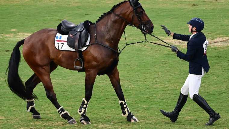 Charles Fernandez habla con el caballo Fluoriet intentando calmarlo luego de caerse durante la competencia individual masculina de equitación. (Foto Prensa Libre: AFP)