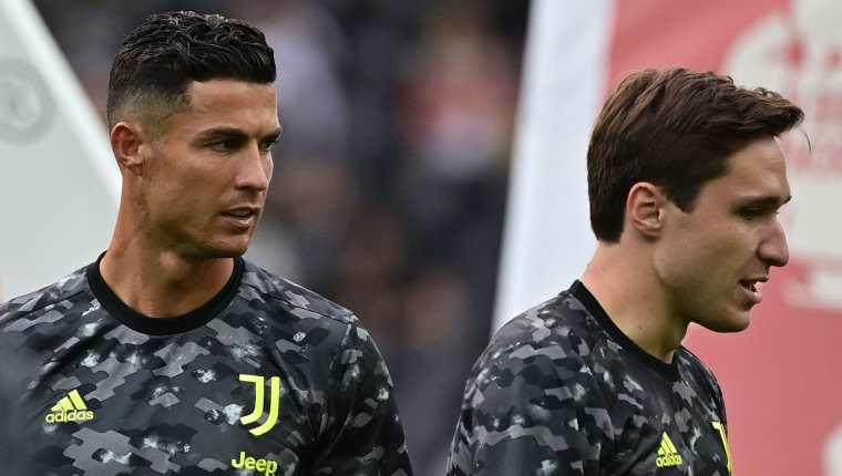 Cristiano Ronaldo (I) y Federico Chiesa calientan antes de enfrentar al Udinese en el Dacia Arena Stadium. (Foto Prensa Libre: AFP)