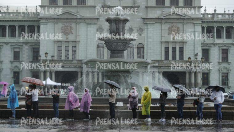 Decenas de guatemaltecos esperan bajo la lluvia para ser vacunados en el puesto habilitado en la Plaza de la Constitución. Fotografía: Prensa Libre (Esbin García).