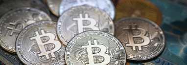 La fotografía ilustrativa tomada el 19 de julio de 2021 en Estambul muestra un billete físico y las imitaciones de la moneda criptográfica Bitcoin. (AFP)