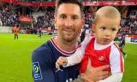 Lionel Messi sostiene en brazos al hijo del portero del Reims Predrag Rajkovic después de debutar en la victoria del PSG ante los rojiblancos. (Foto Prensa Libre: Movistar Deportes Twitter)