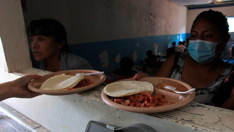 """Migrantes centroamericanos contagiados en su mayoría por covid-19 reciben alimentos en el comedor del albergue """"Esperanza para todos"""", en Ciudad Juárez,  Chihuahua, México. (Foto Prensa Libre: EFE)"""