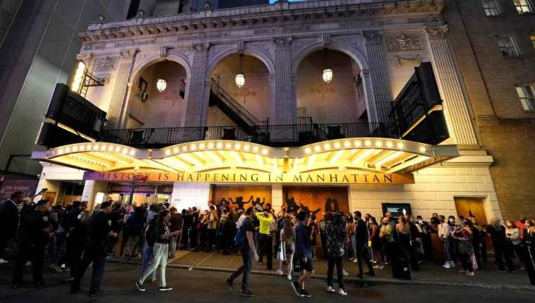 """People wait to attend the Broadway musical """"Hamilton"""" after showing their vaccination cards on September 14, 2021 at the Richard Rodgers Theatre in New York, as the highest grossing Broadway musical of all time returns after being dark for 18 months due the coronavirus pandemic. - Lion King, Wicked and Chicago also opened for the fully vaccinated (Photo by TIMOTHY A. CLARY / AFP)"""